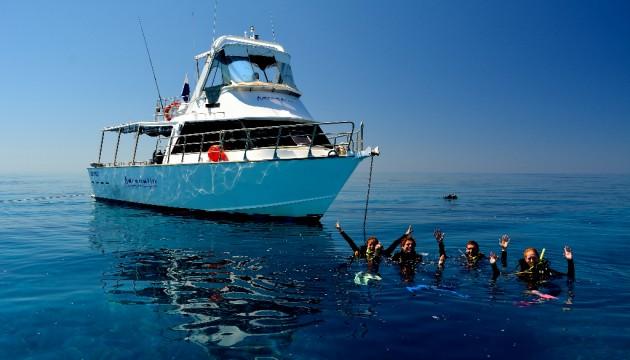 Plongeurs devant un petit bateau dans une mer d'huile