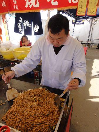 Cuisinier préparant des nouilles sautées