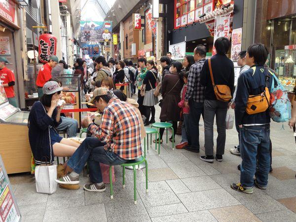 Queue devant un stand de takoyaki à Namba, Osaka, Japon