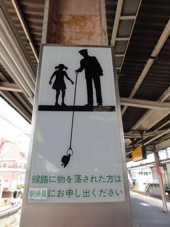 Pictogramme japonais: ne descends pas sur les voies pour aller chercher ton chapeau qui s'est envolé